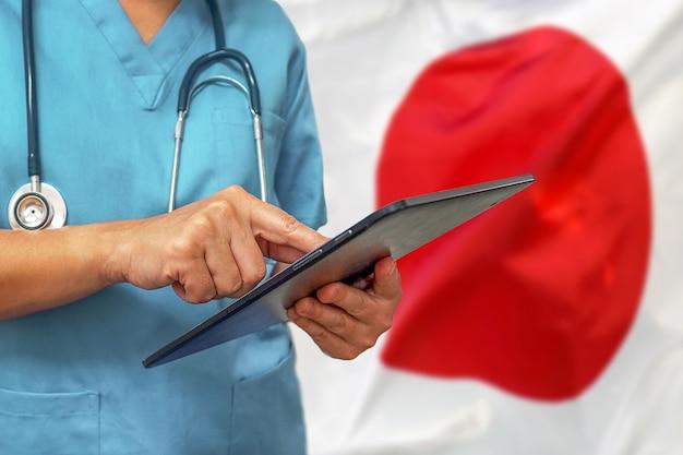 日本の国旗の背景にデジタルタブレットを使用して外科医または医師