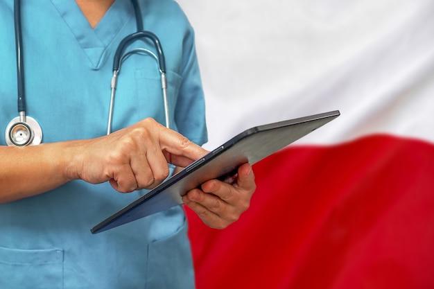 Хирург или врач с помощью цифрового планшета на фоне флага польши