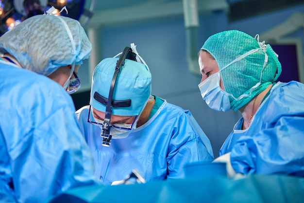 Surgeon performing cosmetic surgery in hospital operating room. surgeon in mask wearing loupes during medical procedure.