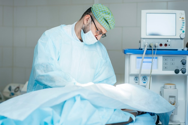 Surgeon performing surgery on breasts in hospital operating room. surgeon in mask wearing surgical loupes during medical procedure.