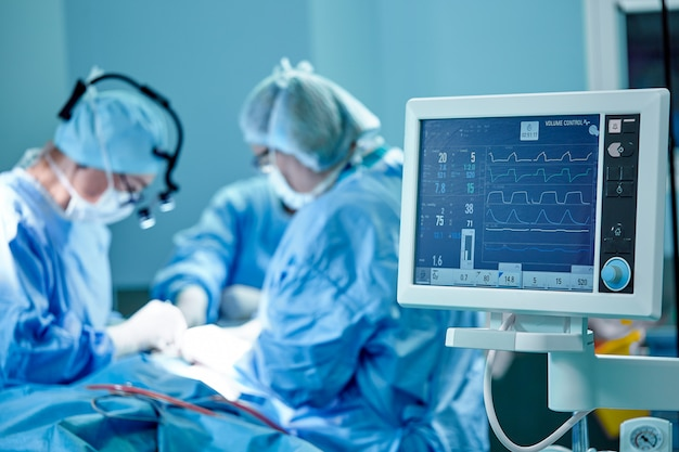 A surgeon's team in uniform performs an operation on a patient at a cardiac surgery clinic. modern medicine, a professional team of surgeons, health.