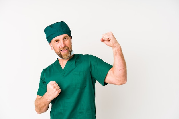 Surgeon senior man isolated on white wall raising fist after a victory, winner concept.