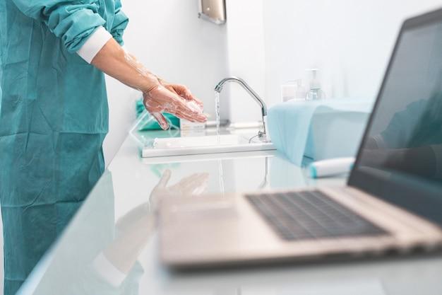 コロナウイルスの発生中に病院内で手術する前に外科医が手を洗う