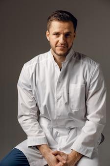 外科医は医療用ローブを着ています。ハンサムな医者のポーズ
