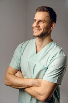 医療ローブの笑顔とポーズで身に着けている外科医。ハンサムな幸せな医者のポーズ