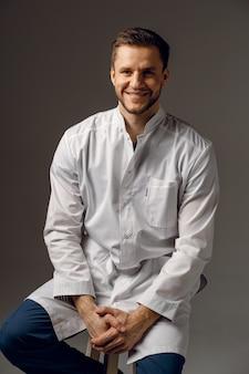 医療ローブの笑顔で身に着けている外科医。ハンサムな幸せな医者のポーズ