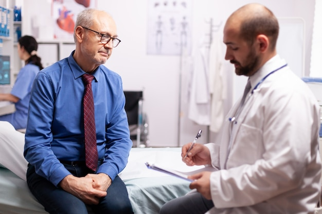 Surgeon wearing stethoscope discussing treatment in examination room with senior man