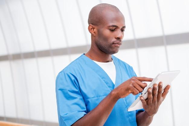 デジタルタブレットを持っている外科医。デジタルタブレットに取り組んでいる青い制服を着た陽気な若いアフリカの医者