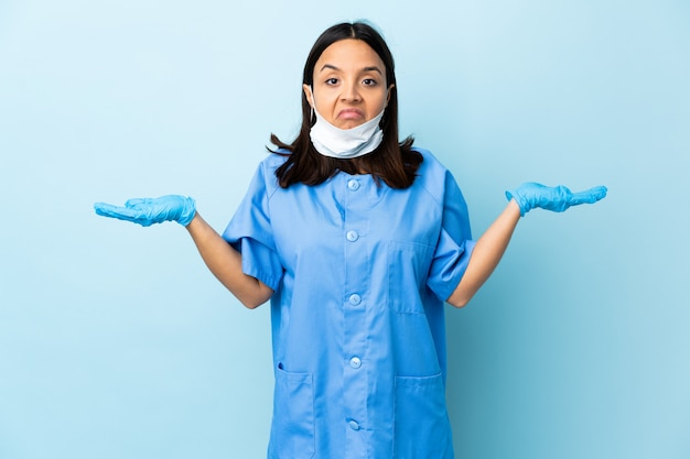 Surgeon woman over blue wall having doubts while raising hands