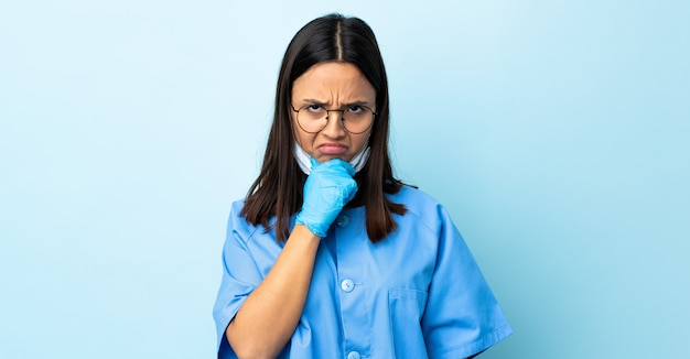 Surgeon woman over blue wall having doubts