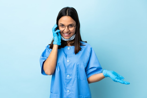 Surgeon woman over blue wall keeping a conversation with the mobile phone with someone