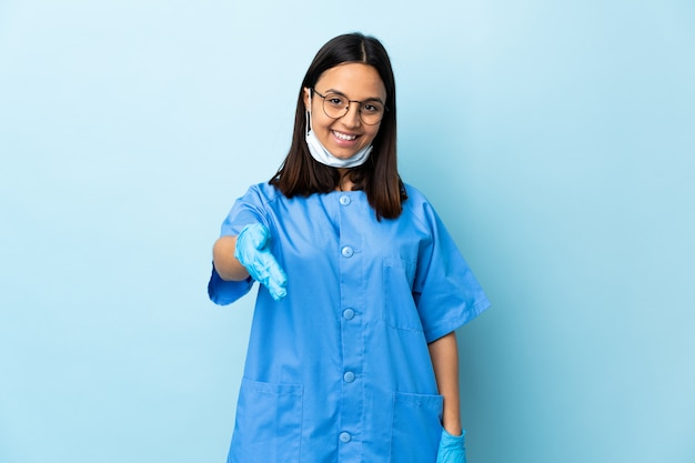 Surgeon woman over blue wall shaking hands for closing a good deal