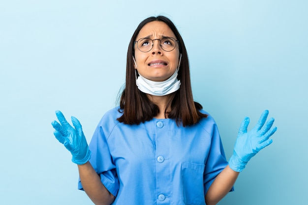 Surgeon woman over blue wall stressed overwhelmed