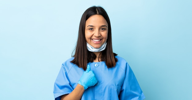 Surgeon woman over blue wall with surprised facial expression