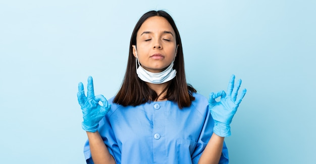 禅のポーズで青い壁に外科医の女性