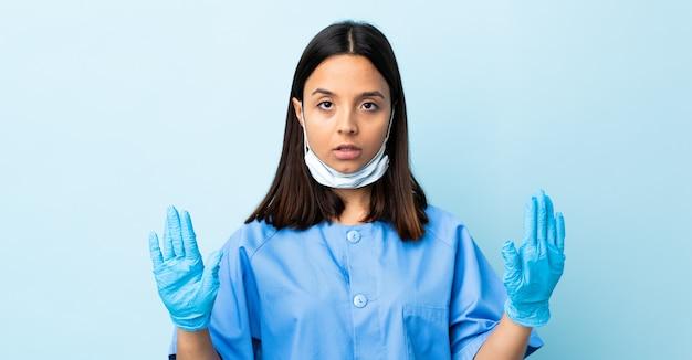 Женщина хирург над синей стеной делает жест остановки и разочарован