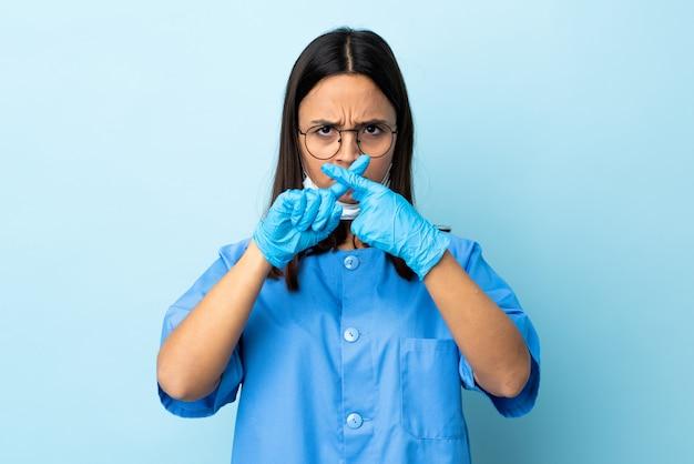 Женщина хирург над синей стеной, делая остановки жест рукой, чтобы остановить поступок