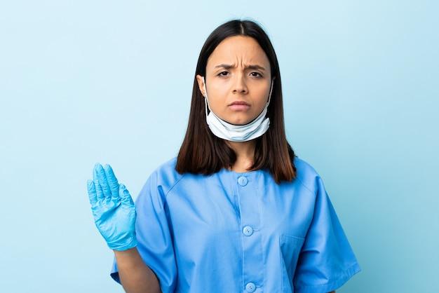 Хирург женщина над синей стеной, делая остановки жест