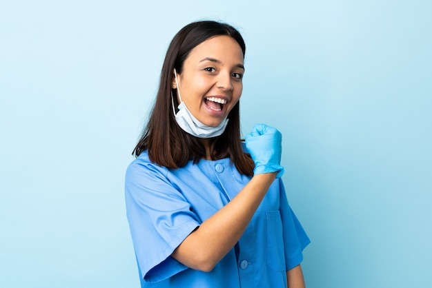 승리를 축하 고립 된 파란색 벽에 외과 의사 여자