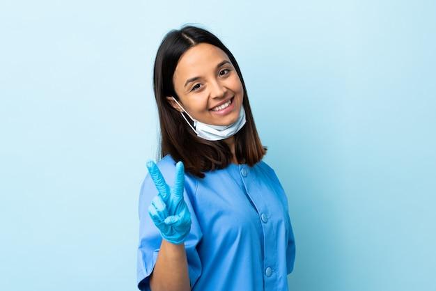 웃 고 승리 기호를 보여주는 고립 된 파란색 벽을 통해 외과 의사 여자