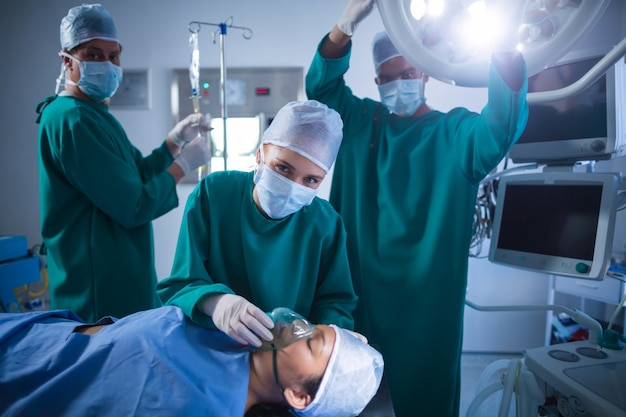 Surgeons adjusting oxygen mask on patient mouth in operation theater