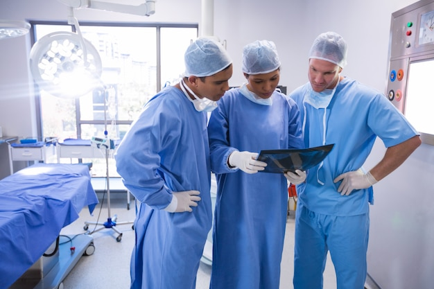 Surgeons examining x-ray in operation room