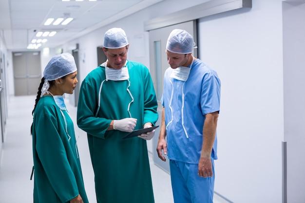 Surgeons having discussion over digital tablet in corridor