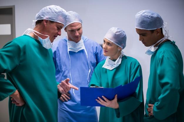 Surgeons having discussion on file in corridor