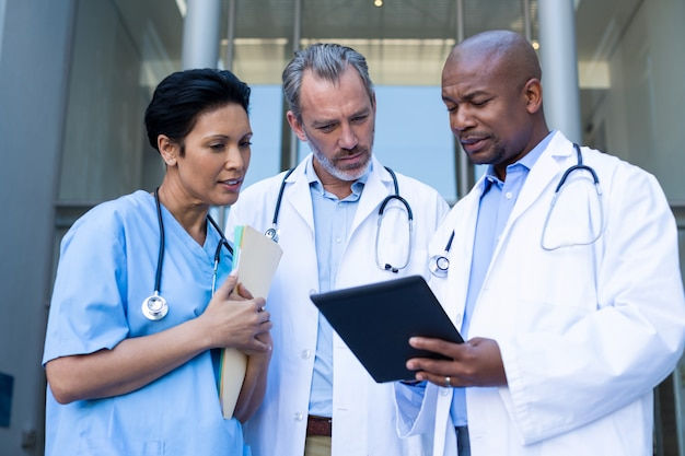 Surgeons and nurse having discussion on digital tablet