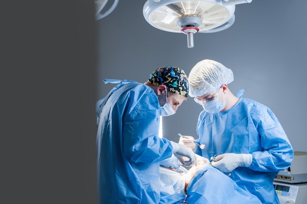 Surgeons do plastic operation in medical clinic. correcting form of face for patient
