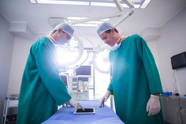 Хирурги с использованием цифрового планшета в операционном зале