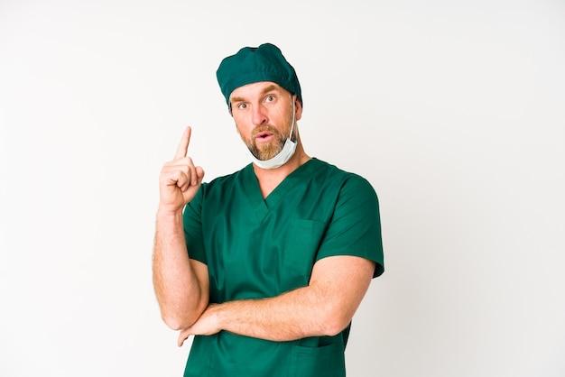 いくつかの素晴らしいアイデア、創造性の隠蔽を持っている白の上に孤立した外科医の年配の男性。
