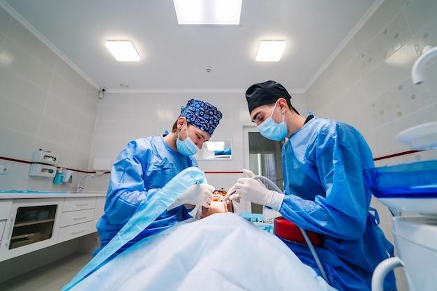 外科歯科手術。 2人の歯科医が口腔病学の手術を行います。歯科医院。セレクティブフォーカス。