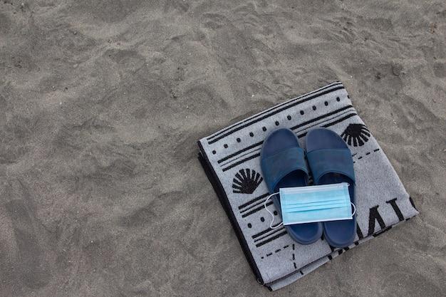 ビーチサンダルの上にある手術用マスクとビーチでのタオル。