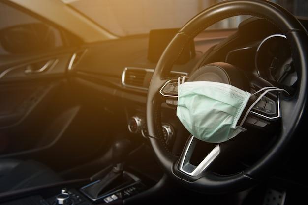 자동차의 스티어링 휠에 장착 된 외과 용 안면 마스크, 코로나 바이러스, covid19, 측면도에 대한 아이디어 및 개념
