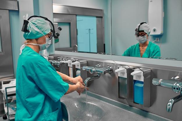 外科的手指消毒:医師は手を洗って、手術の前に手を消毒します。