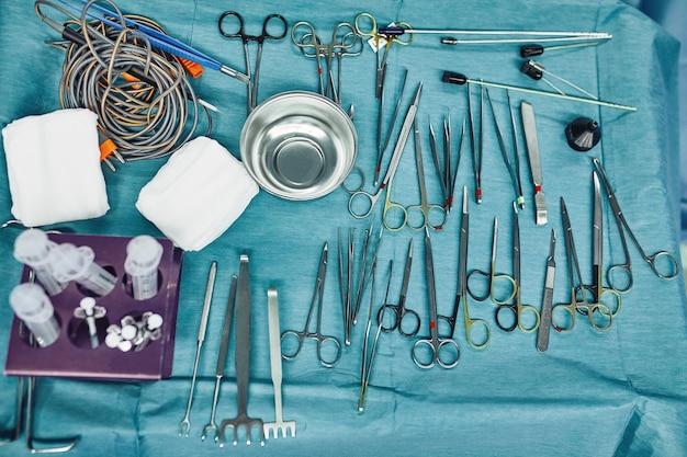 Хирургические инструменты в операционной, разложенные на стерильном столе на специальной голубой ткани.