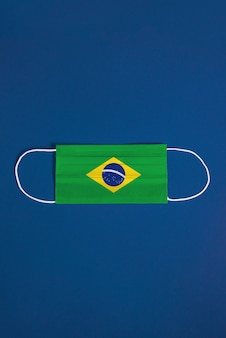 Maschera chirurgica su sfondo blu con bandiera brasiliana
