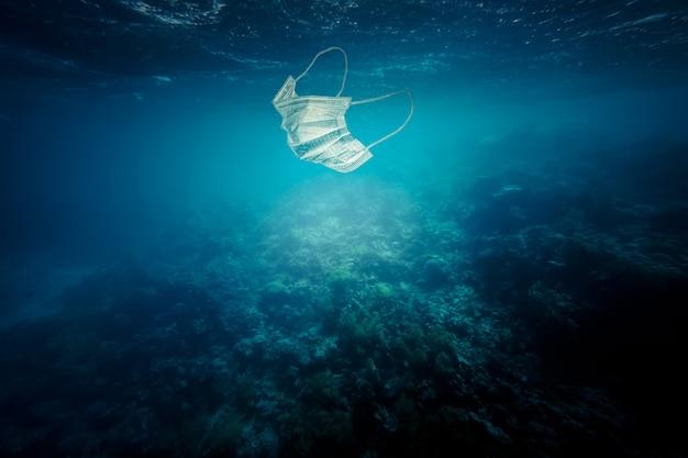 海に浮かぶサージカルマスク。汚染と非生分解性廃棄物の概念。