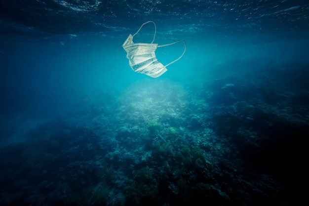 Surgical mask floating in the sea. concept of pollution and non-biodegradable waste.