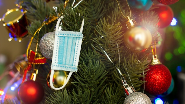 Surgical mask hanging from the christmas tree safe christmas selective focus lens flare