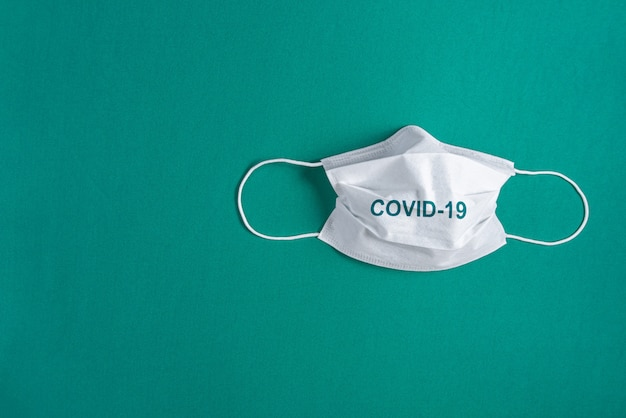 Surgical mask over minimalist green background