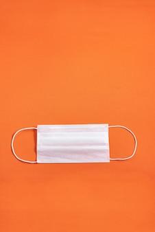 Surgical mask over minimalist orange background