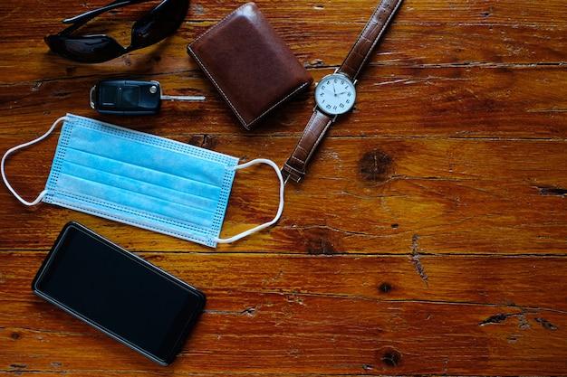Хирургическая маска на столе с часами, смартфоном, кошельком, ключами от машины и солнцезащитными очками на столе