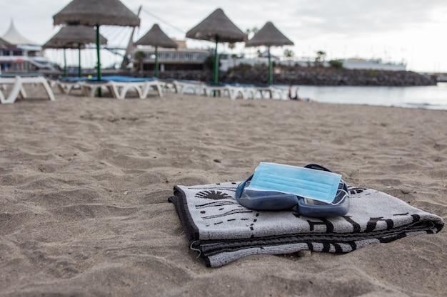 ビーチサンダルのサージカルマスクとビーチのタオル、ビーチの新しい正常性、社会的距離と保護マスク。
