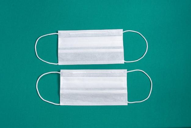 ミニマリストの緑の背景の上の外科用マスク