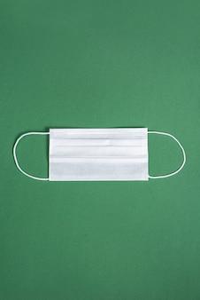 미니멀리스트 녹색 배경 위에 외과 마스크