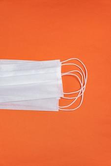 미니멀리스트 오렌지 배경 위에 외과 마스크