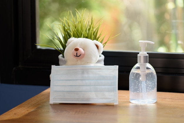 Surgical mask,teddy bear and flower pot on wood table with green nature background