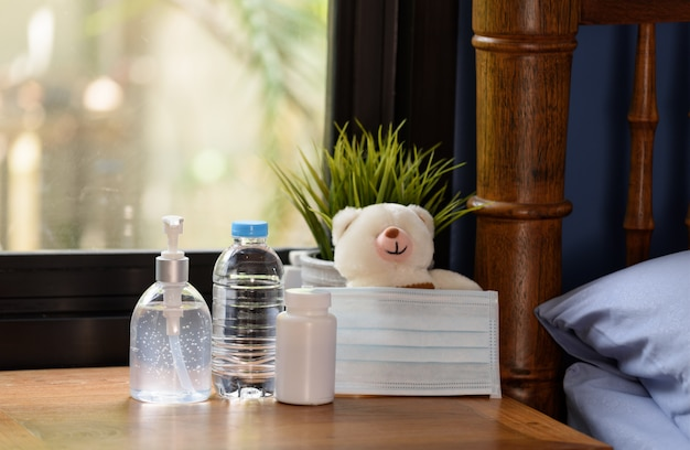 Surgical mask,teddy bear and medicine on wood table with green nature